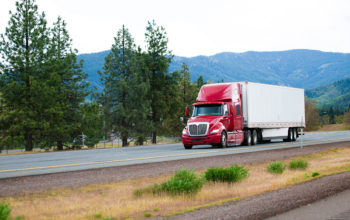Red big rig modern shiny semi-truck with white dry van trailer with aerodynamic skirt move on straight divided interstate highway I-5 in California with green trees and mountains on background