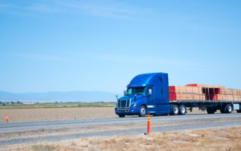 A blue modern big rig semi truck with a high cabin and a flat bad trailer carries stacks of boards reinforced with slings along the road with separated lanes in the opposite traffic direction.